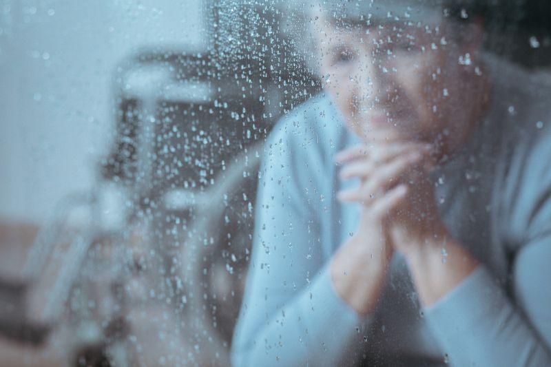 Starsza kobieta za oknem